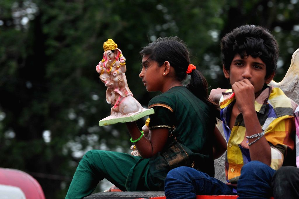 A child takes a Ganesh idol for immersions to Hussain Sagar after Ganesh Festival in Hyderabad on Sept 7, 2014.