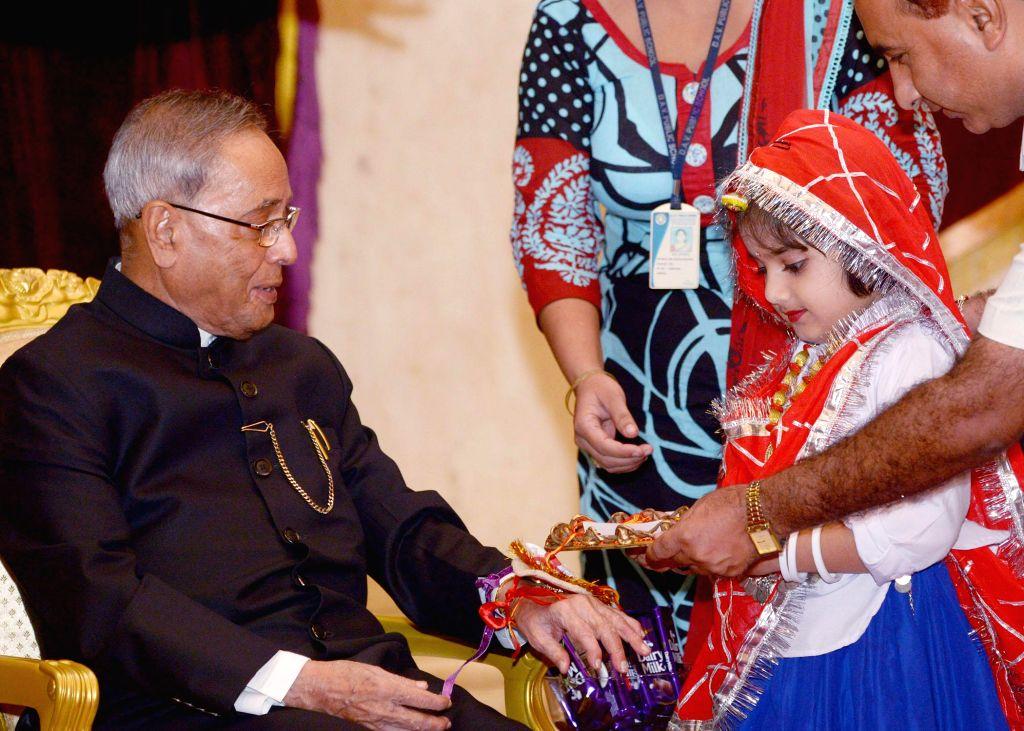 A child ties rakhi on the wrist of President Pranab Mukherjee at Rashtrapati Bhawan in New Delhi on Aug 10, 2014. - Pranab Mukherjee