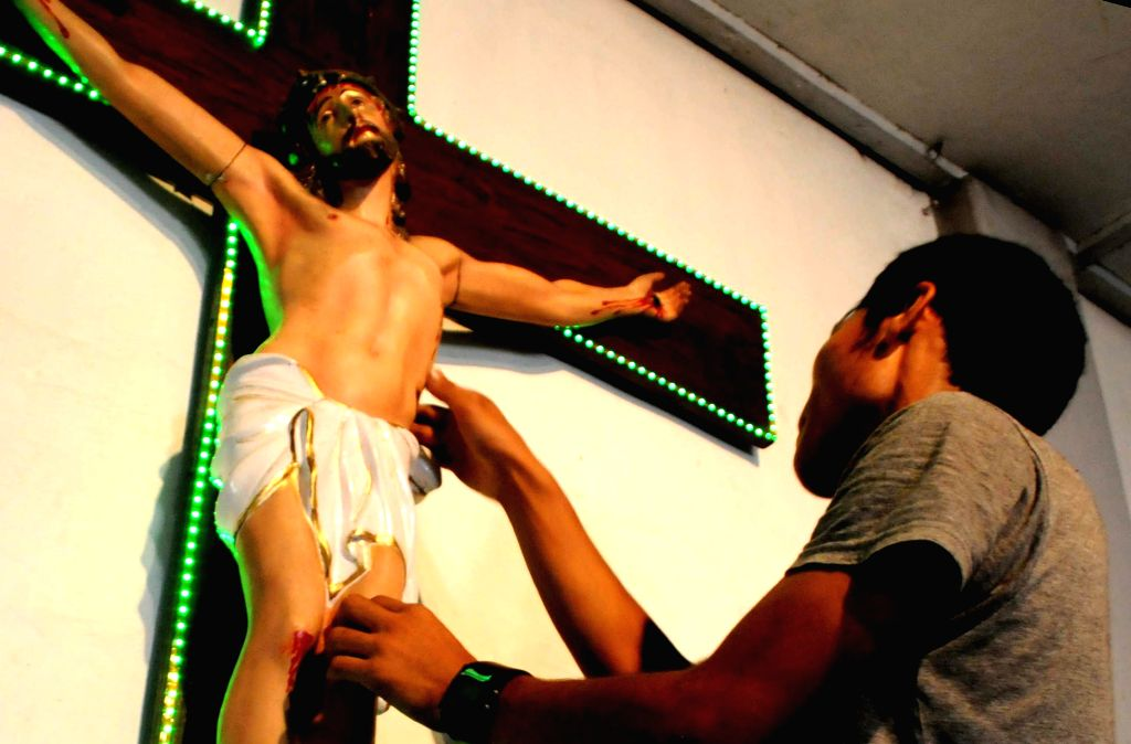 A Christian devotee cleaning the crucifixion of Jesus Christ at a cathedral, on the eve of Good Friday in Agartala, on April 17, 2014.