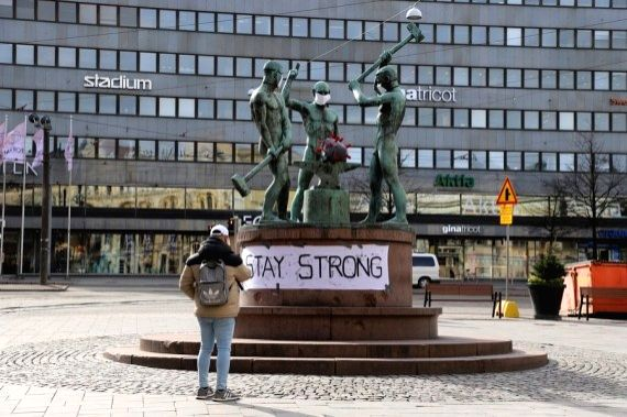 """A citizen takes a picture of the famous city sculpture """"Three Smiths"""" in Helsinki, Finland, March 31, 2020."""