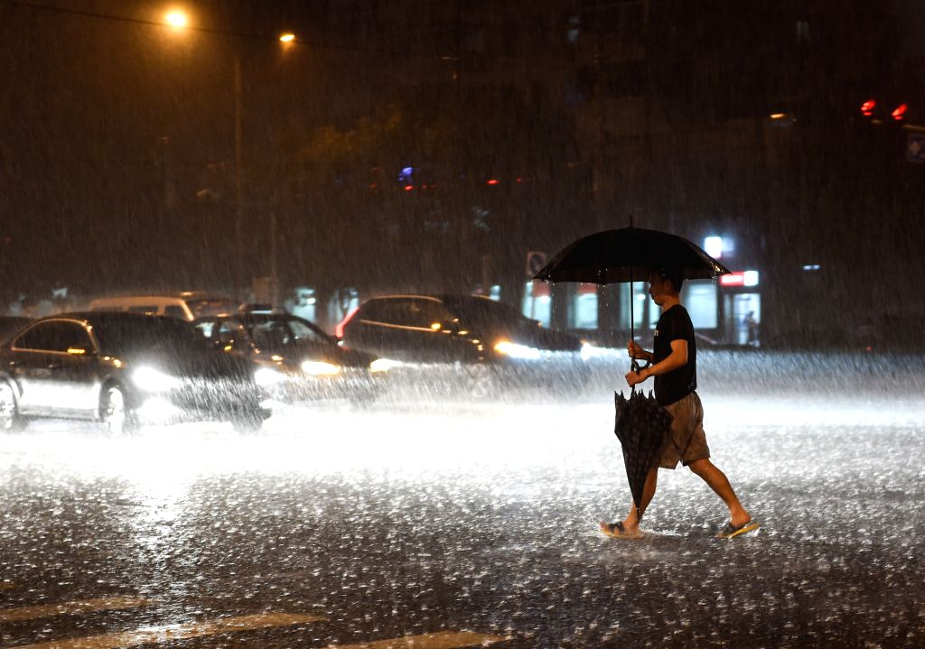 A citizen walks at a rainy night in Beijing, China, July 27, 2015. As heavy rain hit Beijing on Monday, local weather station issued a yellow signal warning for ...