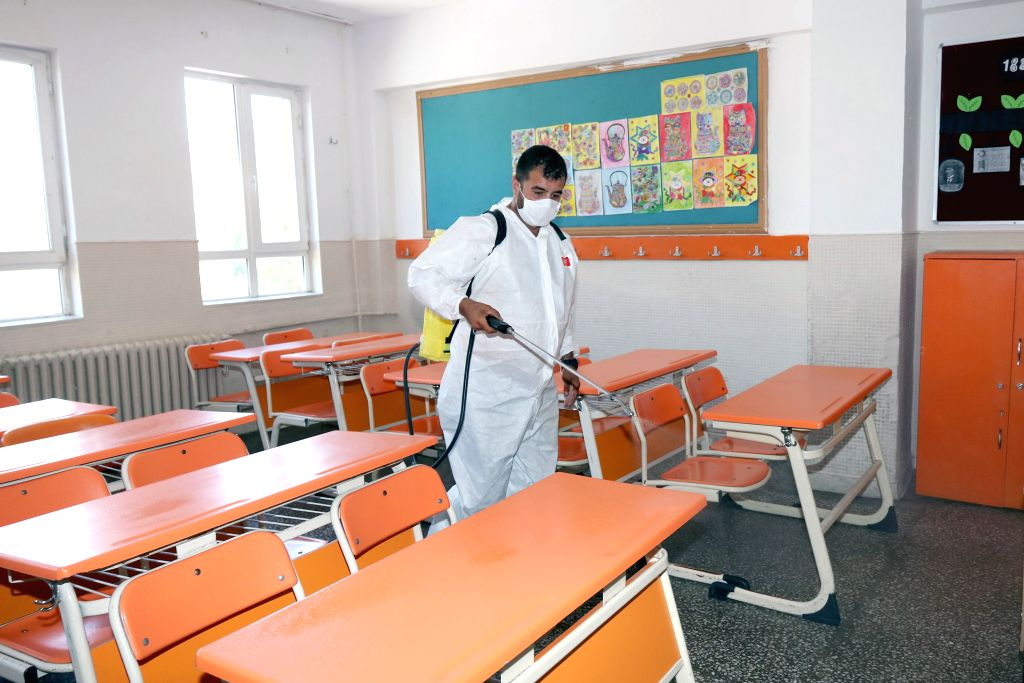 A cleaner disinfects a classroom scheduled to be used for university entrance exams at a school in Ankara, Turkey, on June 25, 2020. Turkey reported 1,458 new ... - Fahrettin Koca
