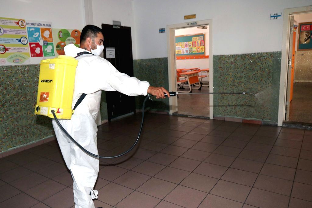 A cleaner disinfects a school scheduled to be used for university entrance exams in Ankara, Turkey, on June 25, 2020. Turkey reported 1,458 new coronavirus cases and ... - Fahrettin Koca