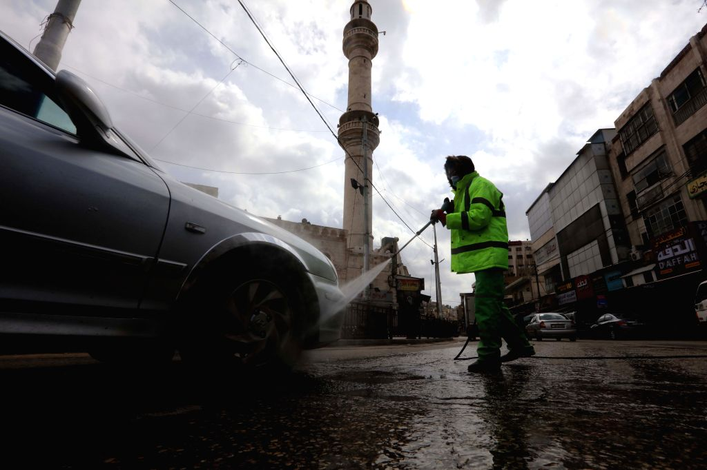 A cleaner sterilizes a car in downtown Amman, Jordan, March 19, 2020. The Jordanian armed forces said on Wednesday that all entrances to the capital Amman will be ...