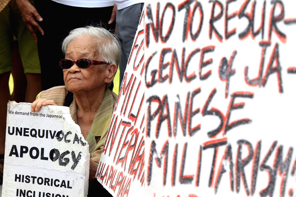 """A """"comfort woman"""" survivor holds a placard during a protest rally in front of the Japanese Embassy in Pasay City, the Philippines, Aug. 14, 2015. ..."""