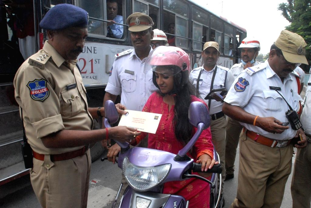 A commuter abiding by traffic rules being presented with a free movie ticket as reward during an awareness drive on road safety organised by the Hyderabad City Traffic Police, on Sep 21, ...