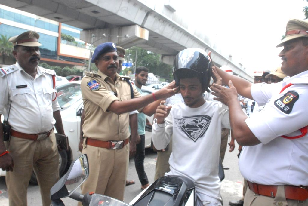 A commuter being made to wear a helmet during an awareness drive organised on road safety by the Hyderabad City Traffic Police, on Sep 21, 2019.