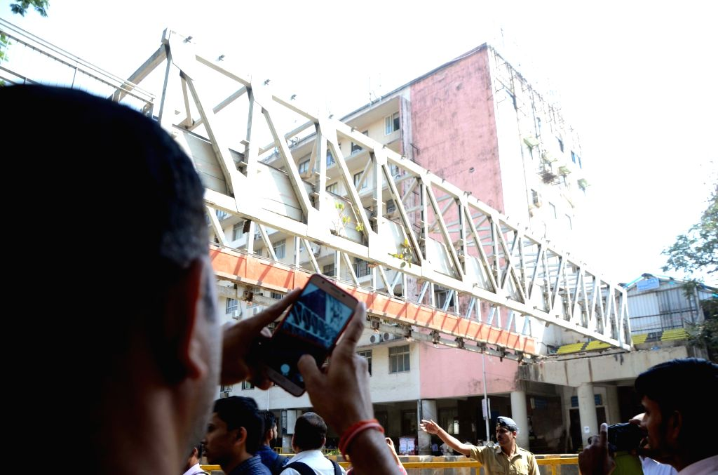 A commuter clicks photos of the pedestrian bridge, a portion of which crashed near the Chhatrapati Shivaji Maharaj Terminus, in Mumbai on March 15, 2019.
