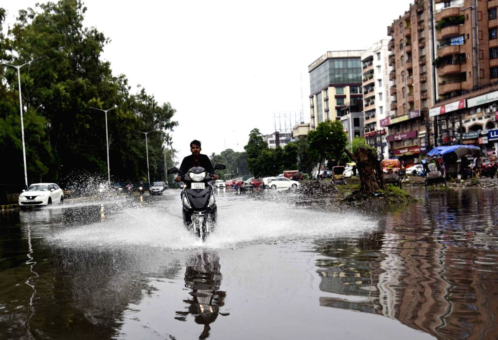 A commuter wades through a water-logged Patna road after heavy rains lashed the city on July 31, 2020.