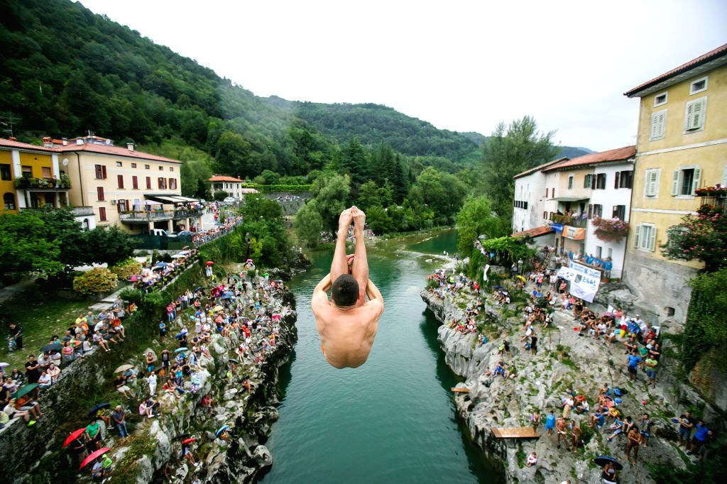 A competitor dives from a 17-meter-high bridge across River Soca during the annual diving competition in Kanal, Slovenia, Aug. 16, 2015.