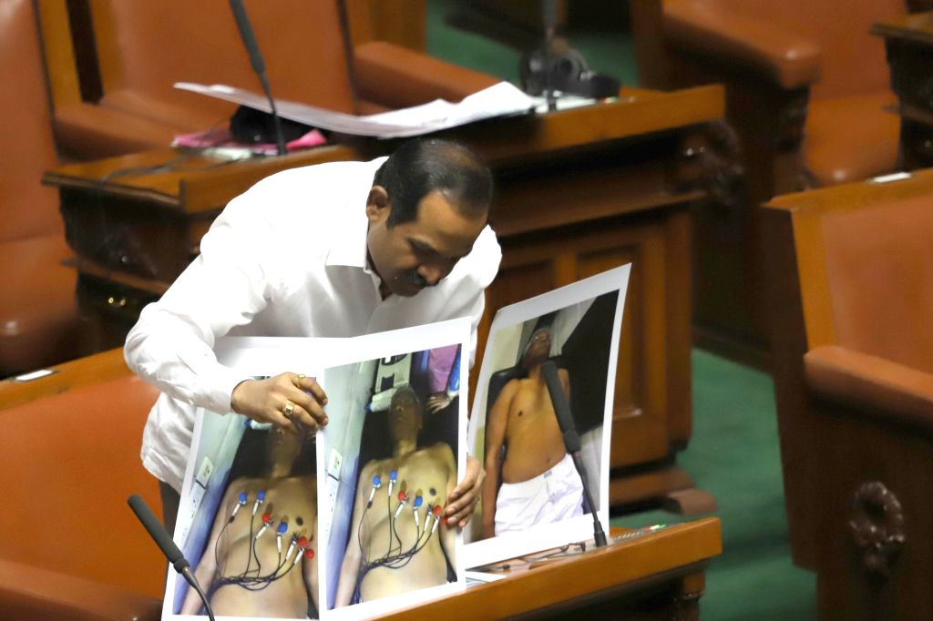 A Congress legislator holds photographs of Shrimant Patil who us is hospitalised, in Karnataka Assembly where Chief Minister HD Kumaraswamy moved motion of confidence in Bengaluru on July ... - Shrimant Patil