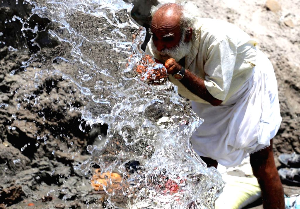 A construction water quenches his thirst on the banks of Ganga river on a hot summer day, in Prayagraj on June 14, 2019.