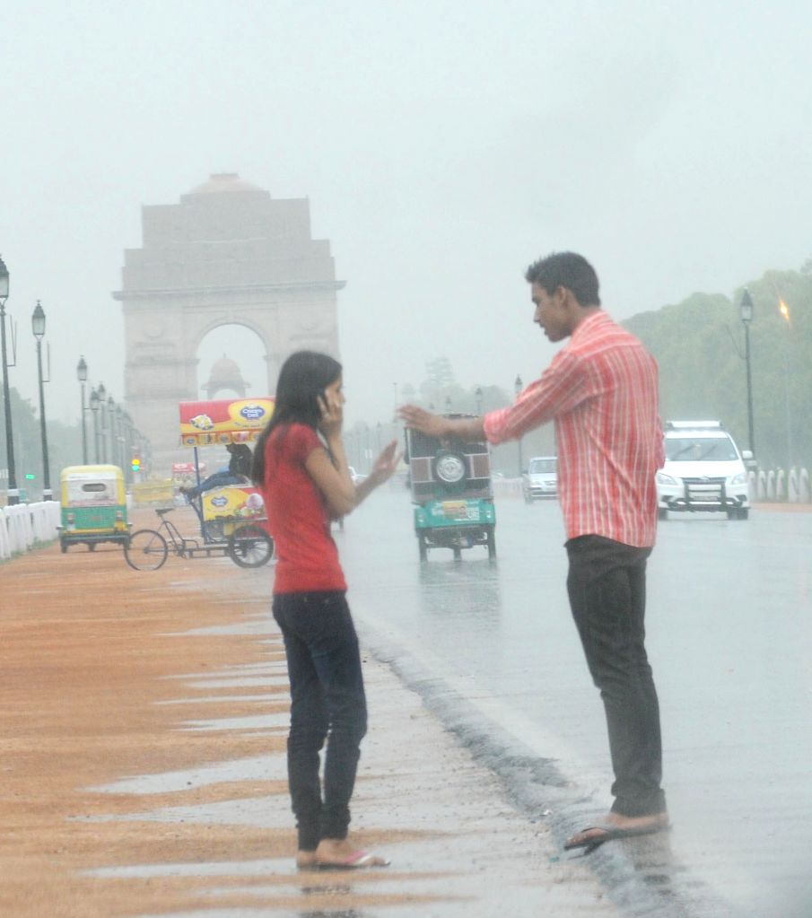 A couple enjoys rains at India Gate lawns in New Delhi on July 6, 2014.