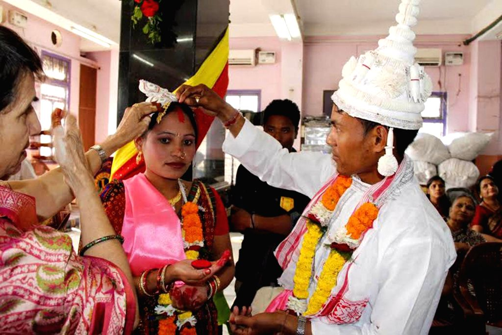 A couple performs ritual as they get married during a community marriage ceremony at Sanganeria Dharamsala in Guwahati on Dec.15, 2013.