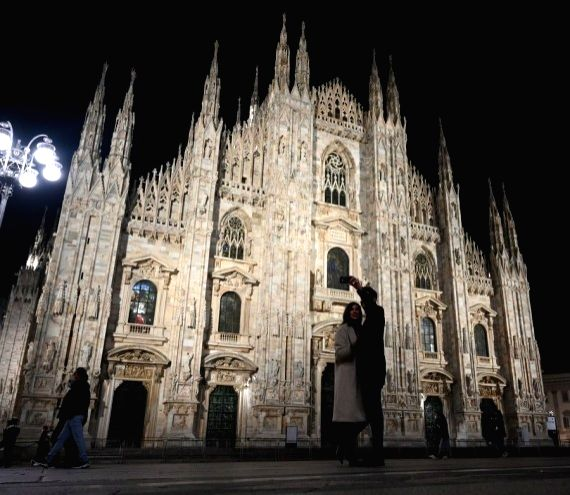 A couple take a selfie at Piazza del Duomo in Milan, Italy, Oct. 24, 2020.