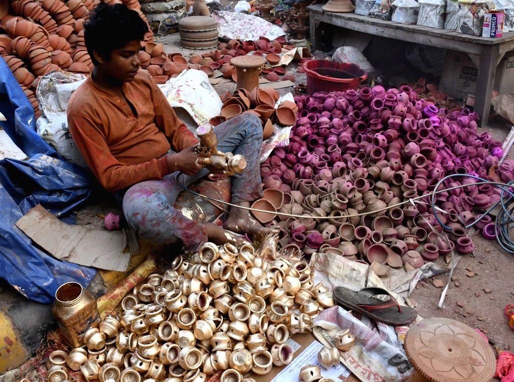 A craftsman paints earthen lamps ahead of Diwali in New Delhi on Oct 25, 2016.