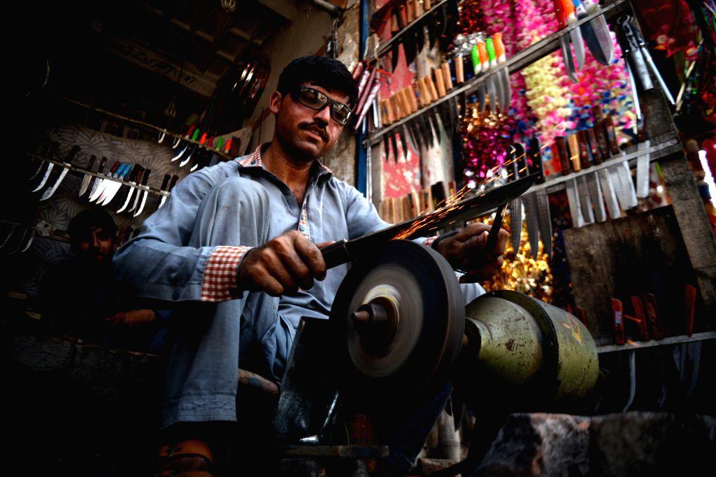 A craftsman sharpens a knife at a shop ahead of Eid al-Adha festival in Peshawar, Pakistan, July 30, 2020.