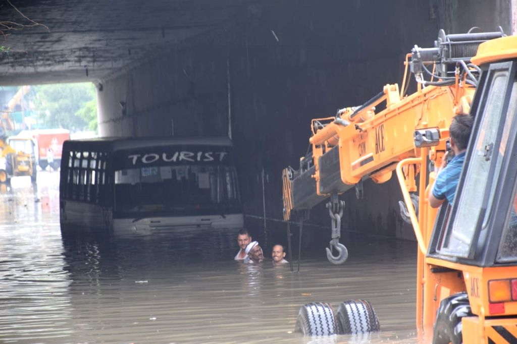 A crane comes to the rescue of a bus submerged under water at an underpass in New Delhi after the national capital received heavy monsoon showers, on Aug 13, 2020.