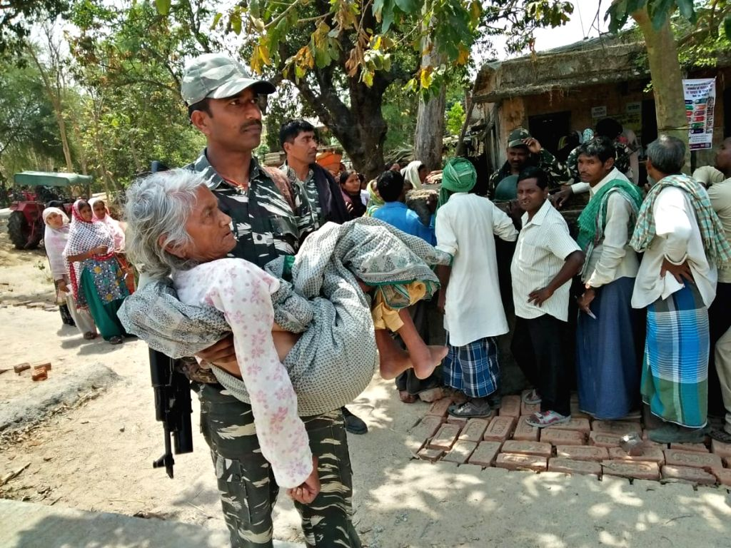 A CRPF personnel assists an elderly woman to a polling booth for casting her vote for the first phase of 2019 Lok Sabha elections in Bihar's Gaya on April 11, 2019.