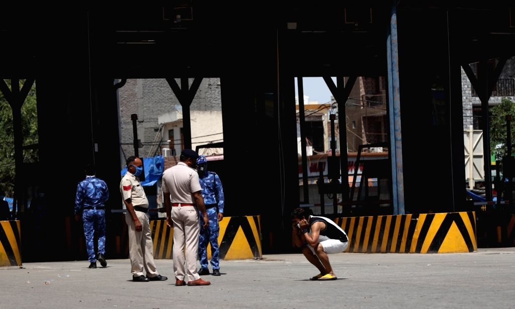 A curfew violator being punished at the Delhi-Faridabad Border that has been sealed in the wake of the countrywide lockdown imposed to contain the spread of novel coronavirus, on March 30, ...