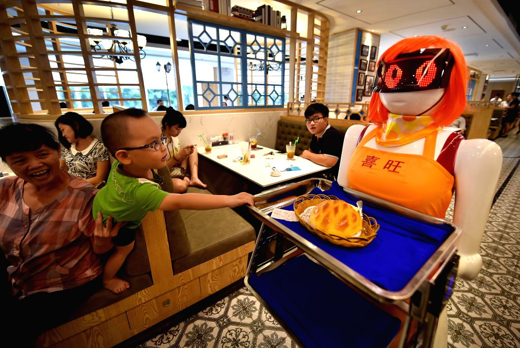 A curious boy reaches for the robot waiter in Haikou, capital of south China's Hainan Province, Aug. 3, 2015. A robot waiter was introduced to a restaurant in ...