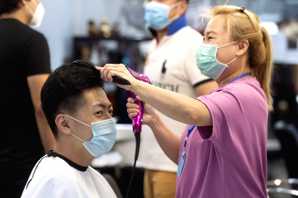 A customer has his hair cut at a barbershop at Chinatown in London, Britain, on July 4, 2020. Millions of people in England emerged from the COVID-19 lockdown on the ...