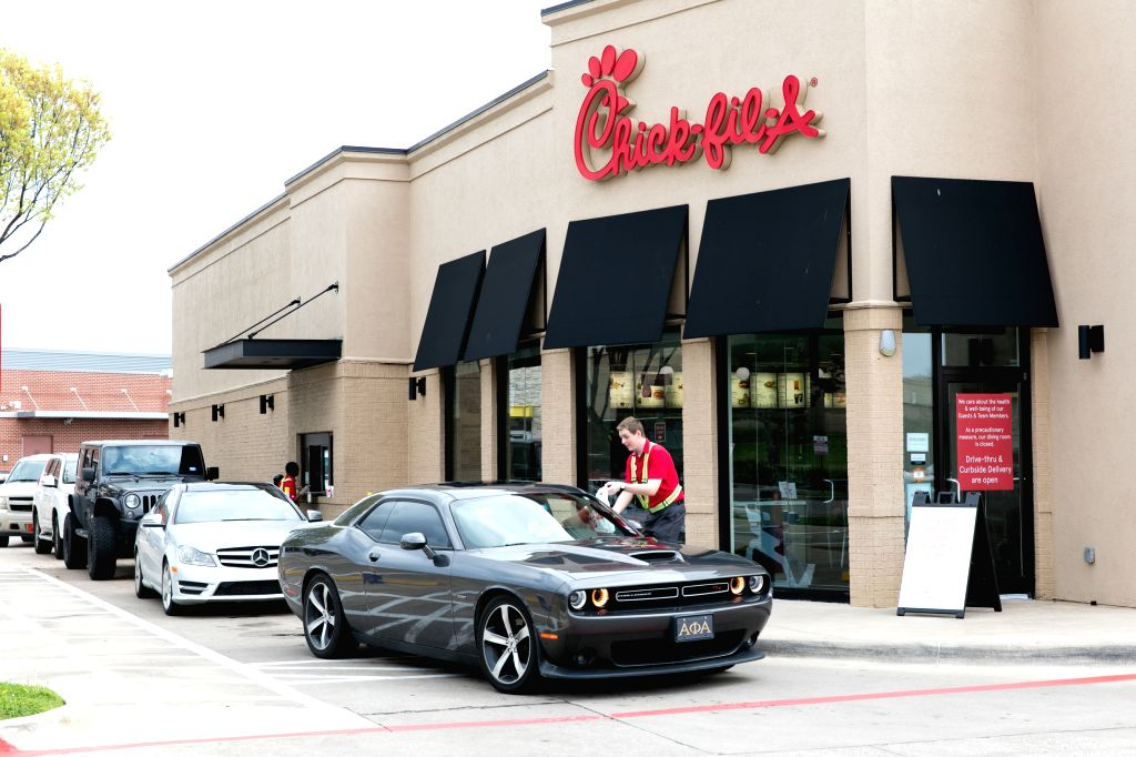 A customer uses Chick-fil-A's drive-thru service in Frisco, on the outskirts of Dallas, Texas, the United States on March 19, 2020. U.S. state of Texas Governor ...