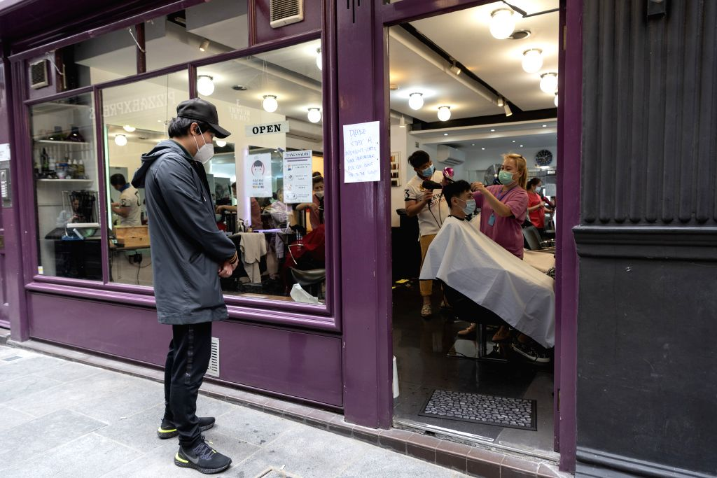 A customer waits outside a barbershop at Chinatown in London, Britain, on July 4, 2020. Millions of people in England emerged from the COVID-19 lockdown on the so ...