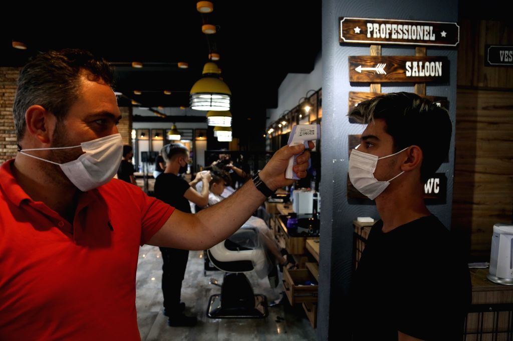 A customer wearing a face mask gets his temperature checked at a hairdressing salon in Ankara, Turkey, on Sept. 12, 2020. Turkey confirmed 1,509 new COVID-19 cases ...