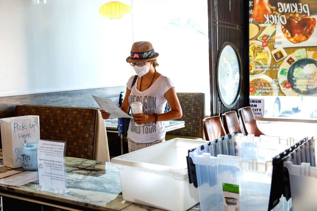 A customer wearing a face mask looks at a takeout menu at a Chinese restaurant in Houston, Texas, the United States, on July 2, 2020. U.S. state of Texas added more ...
