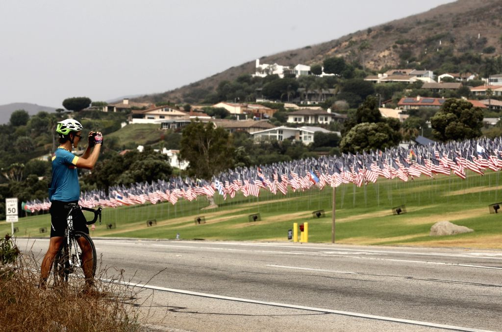 A cyclist takes a photo of the Waves of Flags display at Pepperdine University in Malibu, the United States, on Sept. 11, 2020. The Waves of Flags display ...