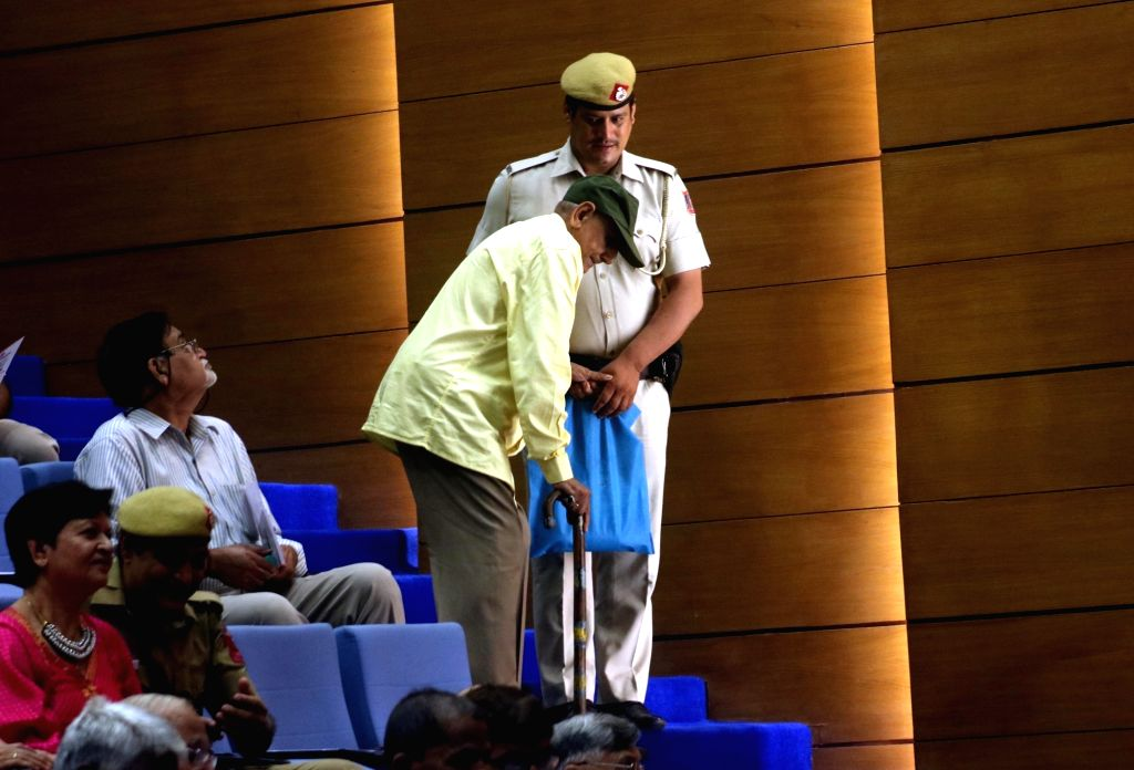 A Delhi police constable helps an elder person who came to attend a programme on International Senior Citizen Day in New Delhi on Oct 1, 2016.