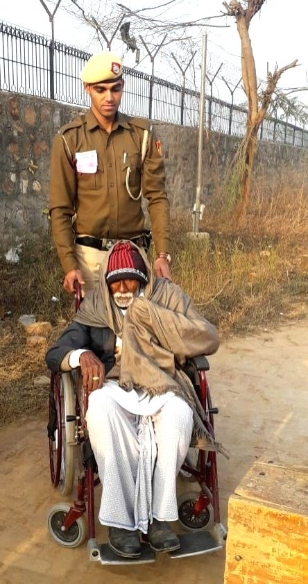 """A Delhi Police personnel assists a senior citizen to the polling station during the Delhi Assembly elections 2020, in New Delhi on Feb 8, 2020. Taking to the Twitter handle @DelhiPolice wrote, """"Helping the citizens in exercising their democratic righ"""