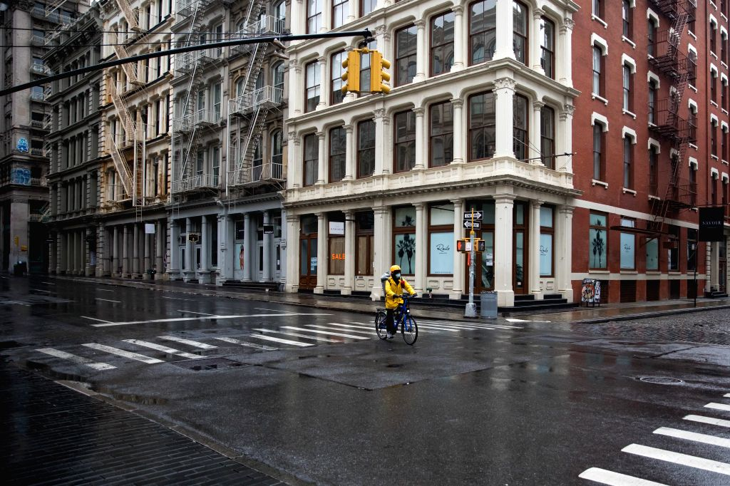A delivery man wearing a face mask passes closed retail stores in New York, the United States, on May 8, 2020. New data showed that U.S. employers cut a staggering ...