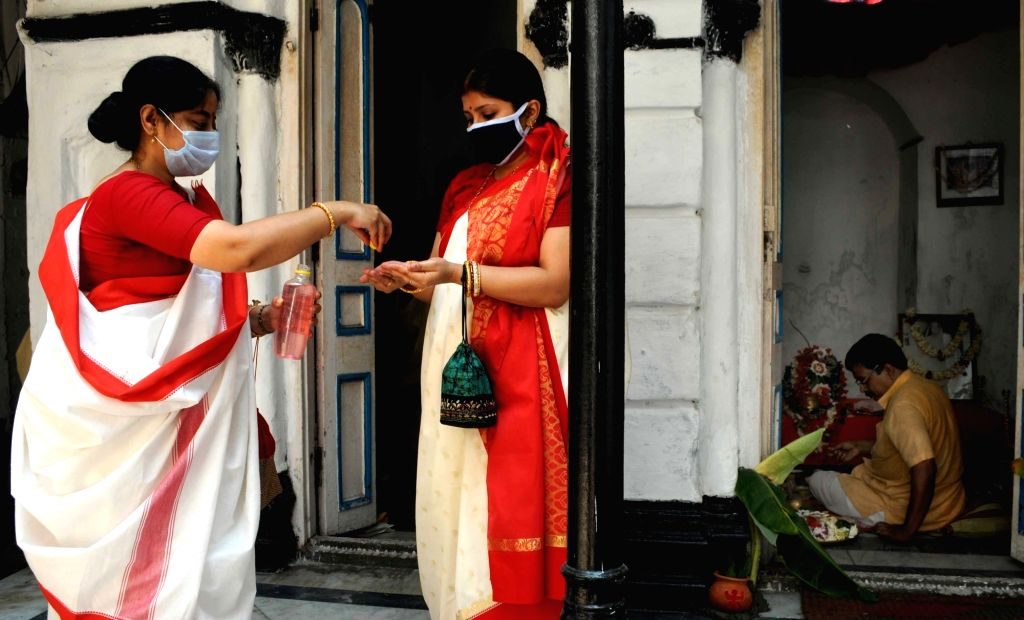 A devotee being provied with hand sanitiser ahead of offering prayers to Goddess Annapurna during the 21-day nationwide lockdown imposed as a precautionary measure to contain the spread of ...