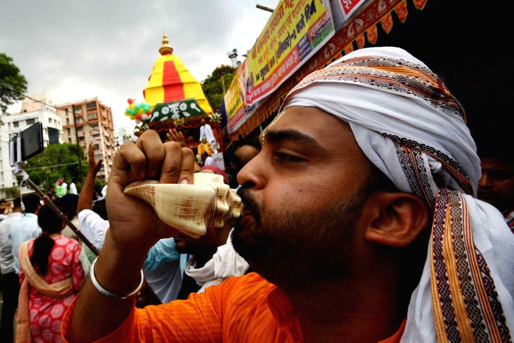 A devotee blows a conch during Jagannath Rath Yatra, in Patna on July 14, 2018.