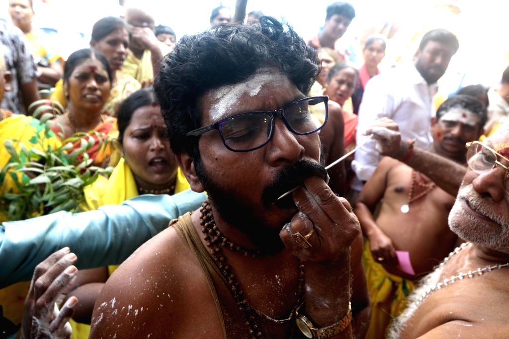 A devotee gets his cheeks pierced with vel skewers before undertaking a procession towards the Murugan temple as part of rituals performed during Thaipusam celebrations, in Chennai on Feb 8, ...