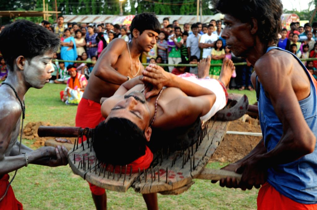 A devotee lays over nails and a machete during Charak festival celebrations in Agartala, on April 13, 2016.