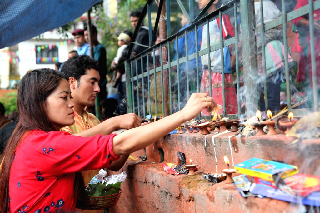 A devotee lights an oil lamp during Nag-Panchami, a Hindu festival for worshipping the serpent deity, in Kathmandu, Nepal, Aug. 19, 2015. The Hindu festival ...