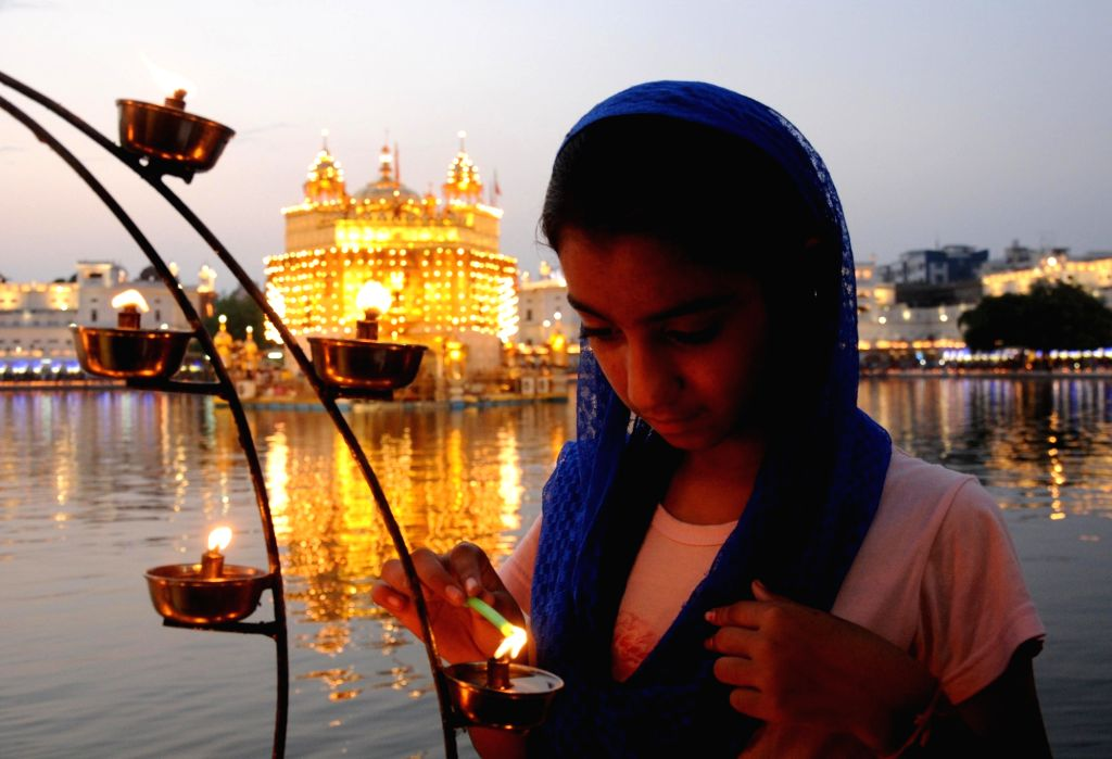 A devotee lights lamps at the Golden Temple on 'Parkash Purab of Sri Guru Granth Sahib' at the Golden Temple in Amritsar on Sept 10, 2018.