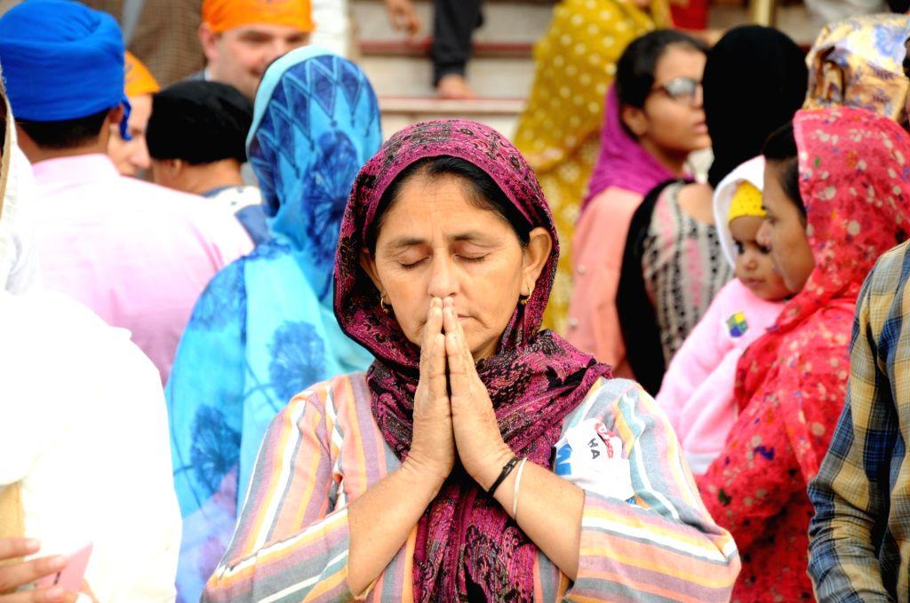 A devotee offers prayers at the Golden Temple during the 550th birth anniversary celebrations of Guru Nanak Dev in Amritsar on Nov 12, 2019. - Nanak Dev