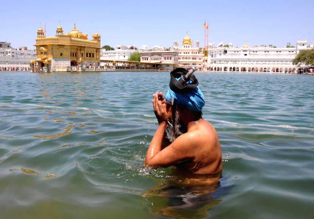A devotee takes a dip in the holy pond at the Golden Temple on the occasion of 'Gurta Gaddi Diwas' of the sixth Sikh Guru, Guru Hargobind Sahib in Amritsar on May 27, 2019.