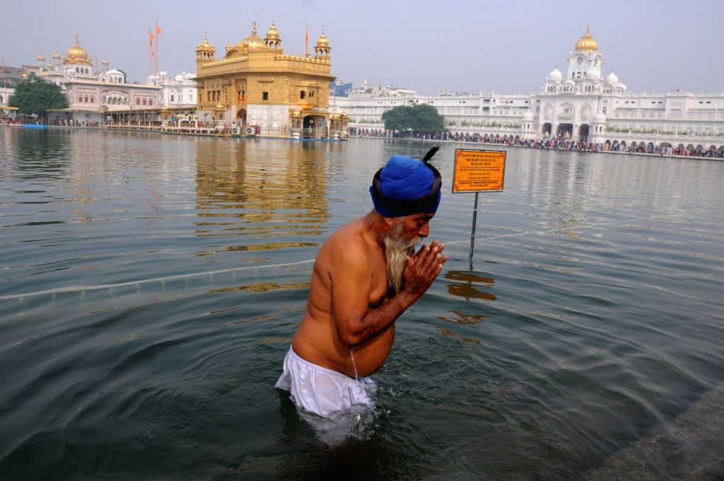 A devotee takes a dip in the holy pond at the Golden Temple during the 550th birth anniversary celebrations of Guru Nanak Dev in Amritsar on Nov 12, 2019. - Nanak Dev