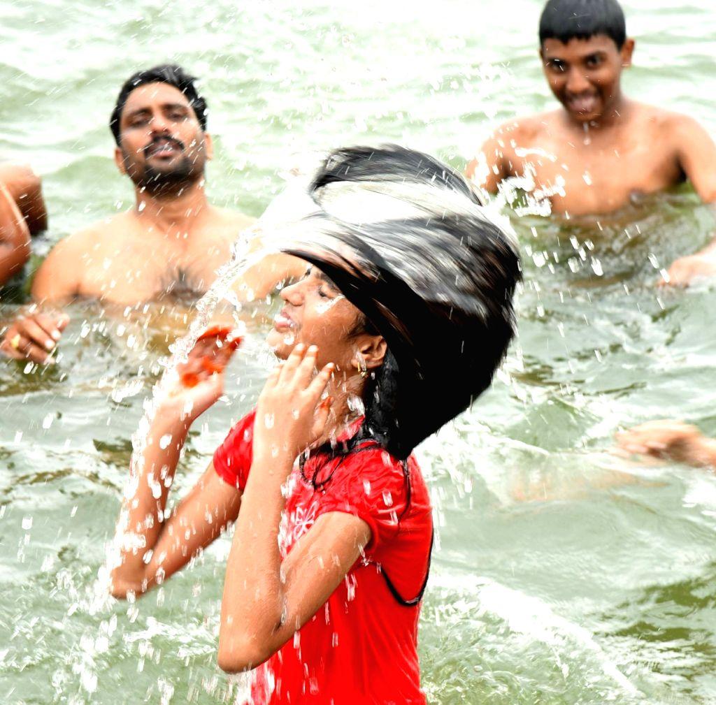 A devotee takes a holy dip during Krishna Pushkaralu river festival in Karimnagar of Telangana on Aug 14, 2016.