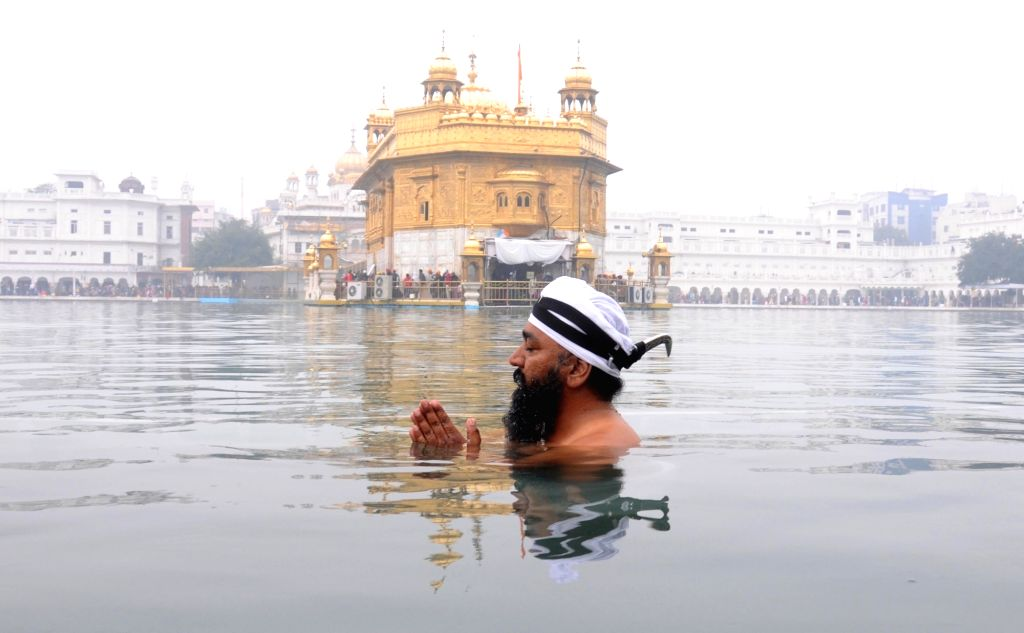 A devotee takes holy dip in a Sarovar at the Golden Temple on the occasion of birth anniversary celebration of the 10th Sikh Guru Gobind Singh in Amritsar on Jan 16, 2016.