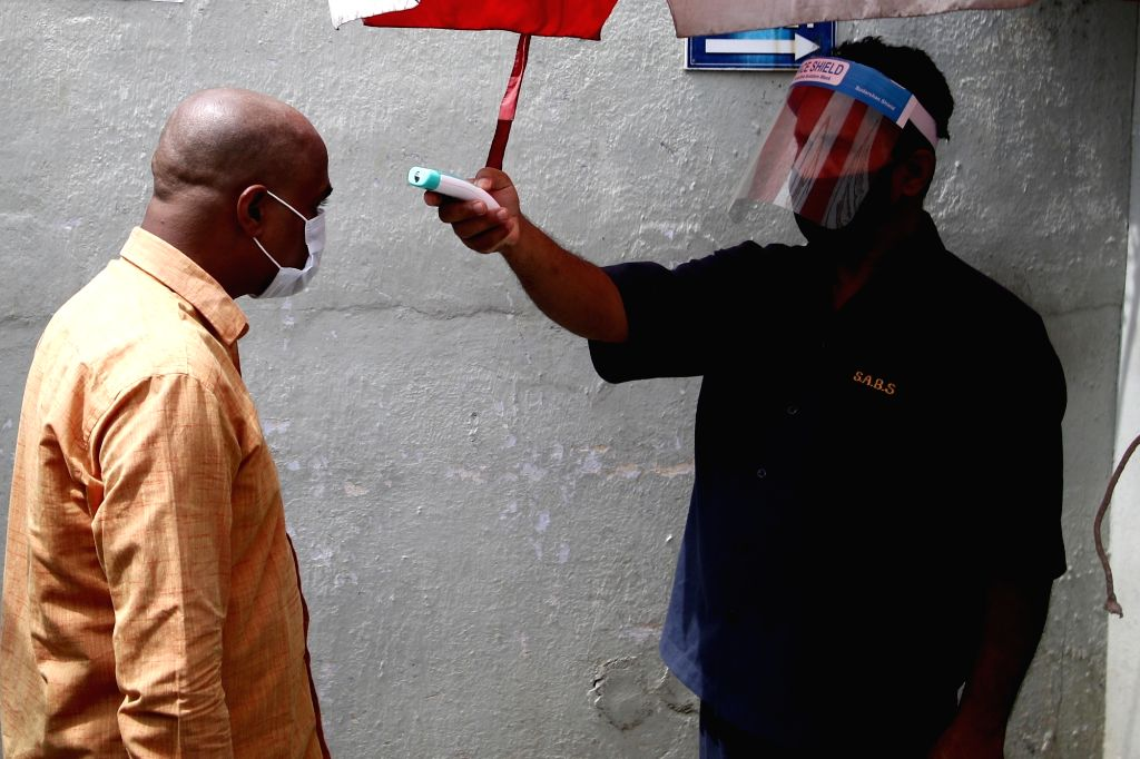A devotee undergoes body temperature check at a temple that reopened after the Tamil Nadu Government permitted the reopening of the places of worship as part of several relaxations that ...