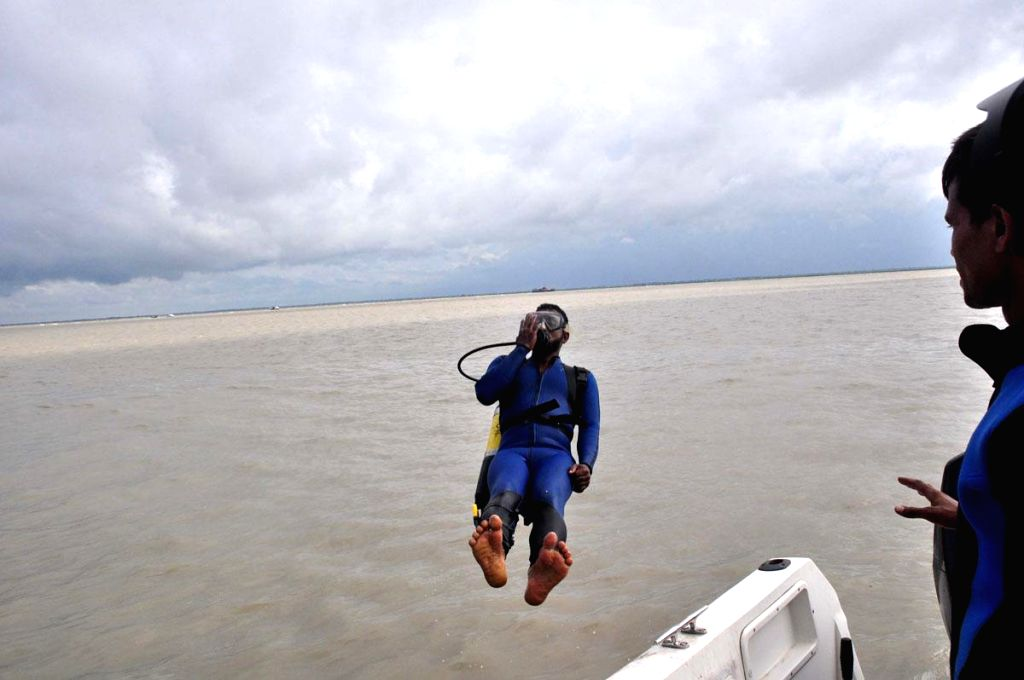 A diver jumps into the Padma river in search of survivors near Mawa, Bangladesh where Pinak-6 - a launch capsized on Aug 4, 2014. The launch had 200 passengers on-board.
