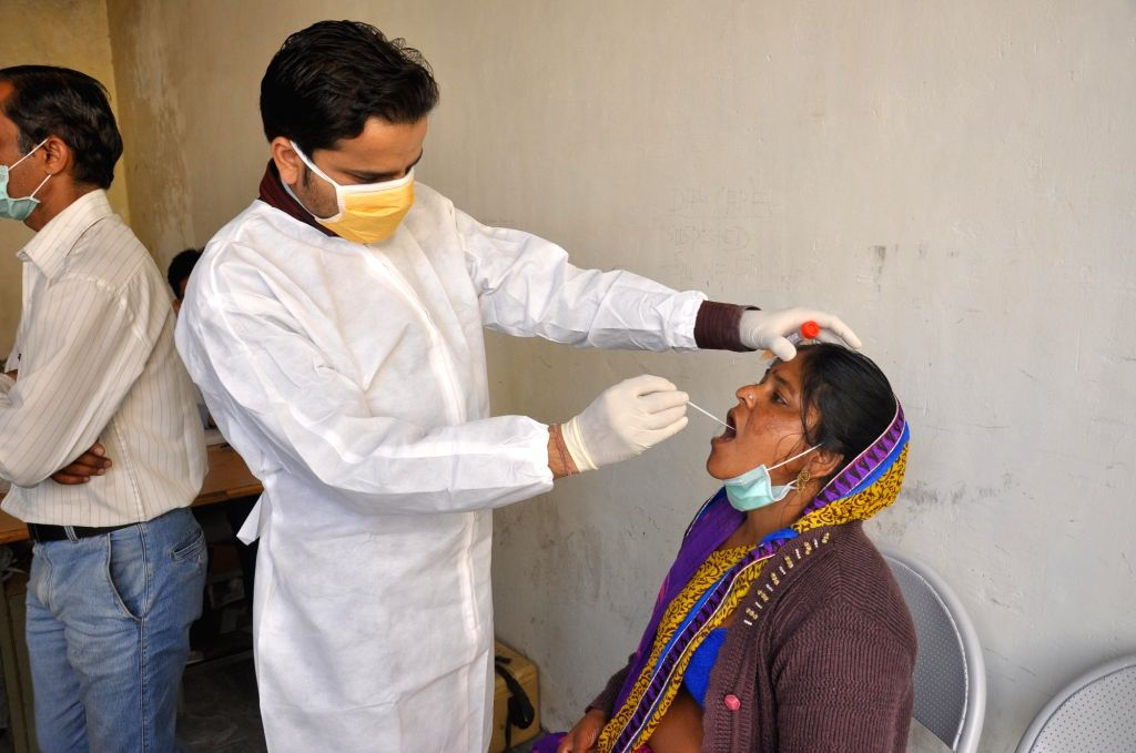 A doctor collects oral swab from a suspected swine flu patient for medical examination. (File Photo: IANS)