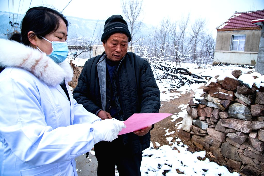 A doctor explains a leaflet on the prevention and control of the novel coronavirus to a resident at Tumen Village of Shuiquan Town in Zaozhuang City, east China's ...