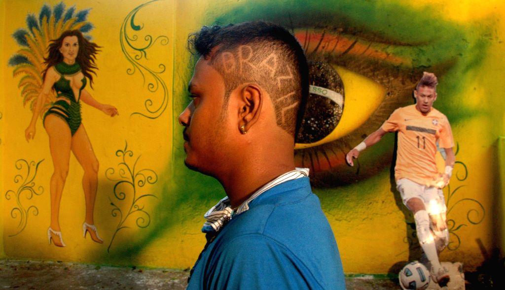 A fan of Brazilian football team shows his new hair cut in Kolkata on June 27, 2014.